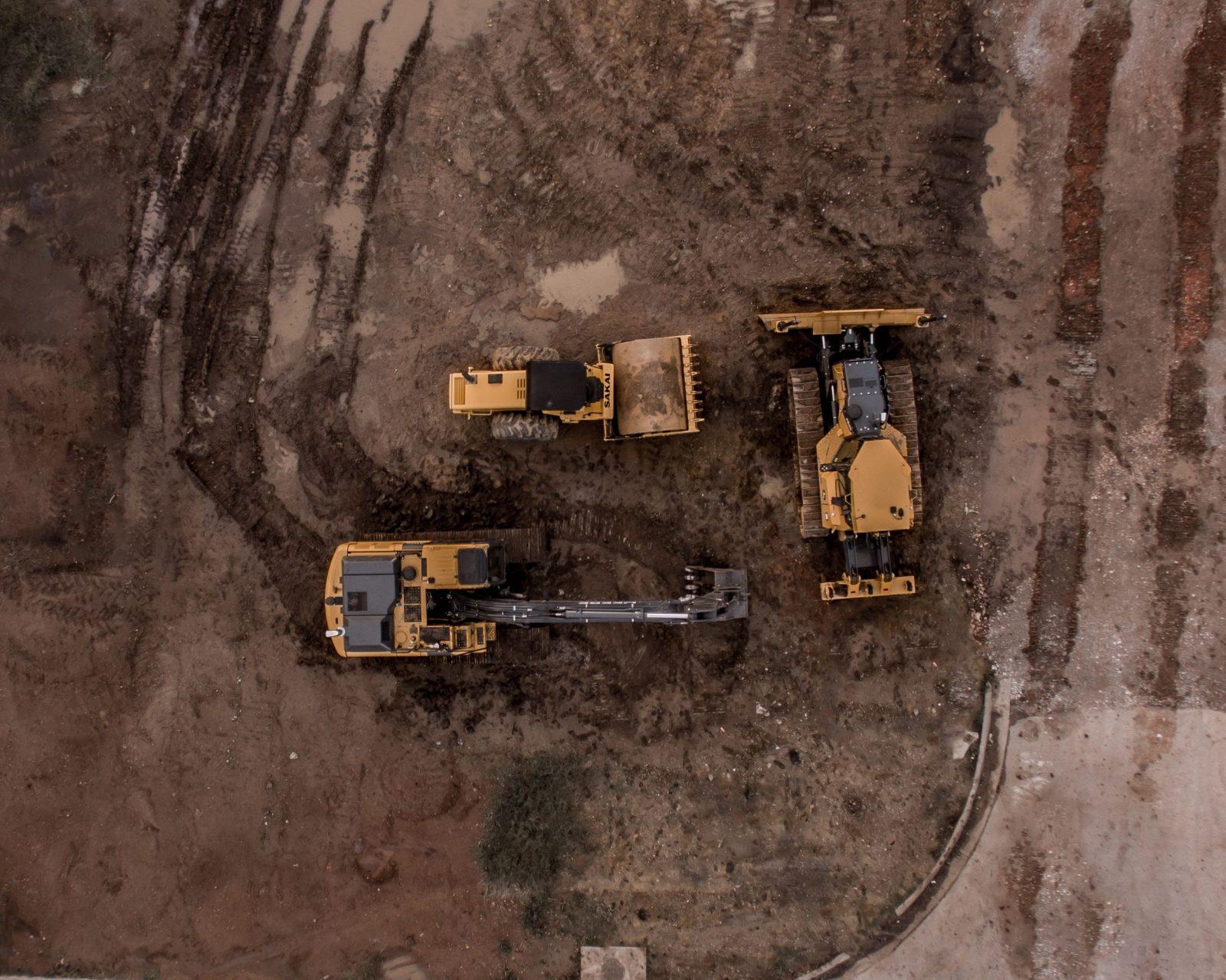 aerial-photo-of-excavator-road-roller-and-bulldozer-157935226